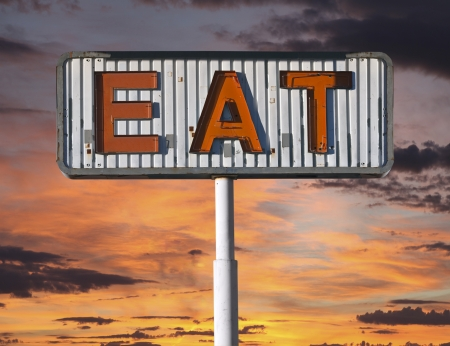 roadsides: Old eat sign with sunset sky.