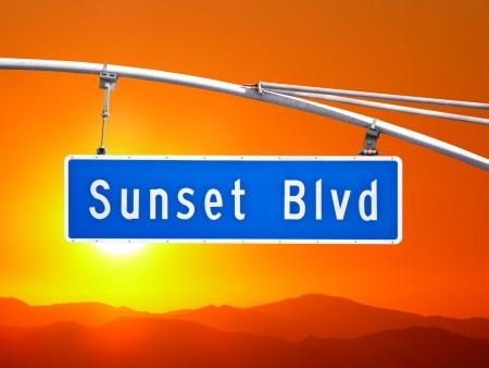 hollywood hills: Sunset Blvd overhead street sign with orange dusk sky.