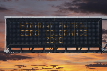 Highway Patrol zero tolerance area electric warning sign with sunset sky  photo