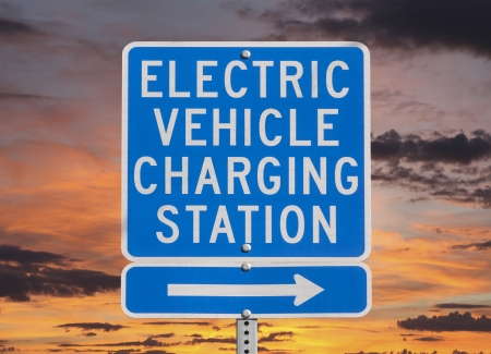 Electric vehicle charging station sign isolated with sunset sky