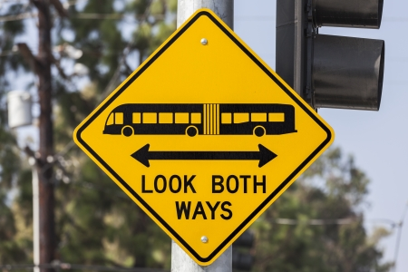 both: Look both ways bus and tram warning sign.