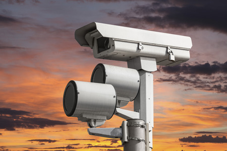 Traffic intersection signal surveillance camera with sunset sky  写真素材
