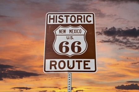 Historic Route 66 New Mexico sign with sunset sky.