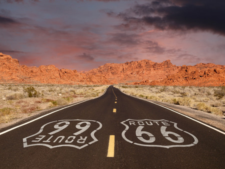 Route 66 pavement sign with Mojave desert red rock mountain sunset.