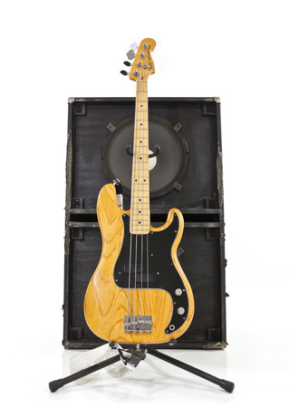 thrashed: Illustrative editorial photo of a vintage Fender Percision bass guitar with a two 15 inch speaker box. Editorial