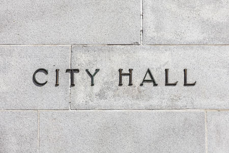 City Hall sign on a stone cold granite wall.