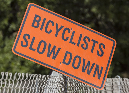 Weathered bicyclists slow down sign in a urban city park. Stock Photo