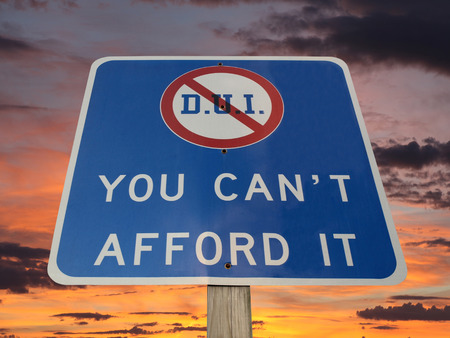drunk driving: DUI you cant afford it warning sign with sunset sky.