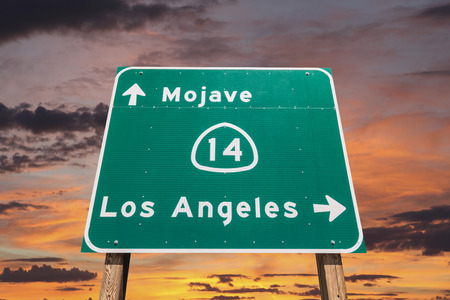 Mojave desert freeway sign towards Los Angeles with sunset sly  Stock Photo