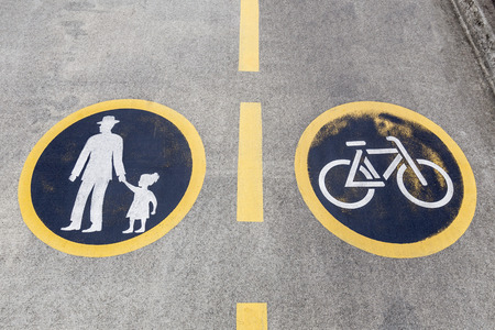 Weathered painted pavement bicycle and pedestrian lanes sign