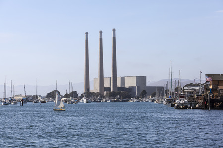 MORRO BAY, CALIFORNIA - July 6, 2014:  Recreational boats moored below towering 450 foot smokestacks of the recently closed power plant in Morro Bay.