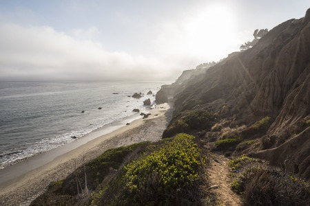 Sun bursting through afternoon fog bank at El Matador State Beach north of Malibu, California  Stock Photo