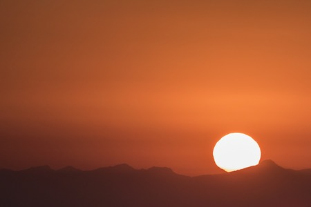 Last light as sun sets into ocean haze beyond the Santa Monica Mountains near Los Angeles, California.   Stock Photo