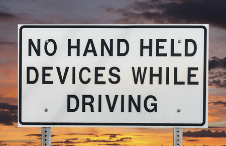 warning signs: No hand held devices while driving sign isolated with sunset sky.