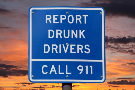 under arrest: Report drunk drivers highway sign with sunset sky.