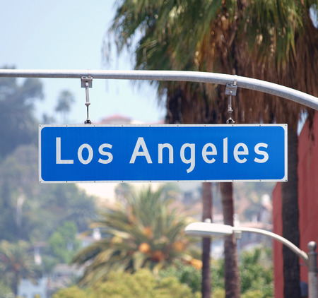 Los Angeles street sign with palm trees in Southern California.