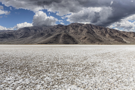 salt flat: Mojave desert dry lake salt flat with dark storm clouds.