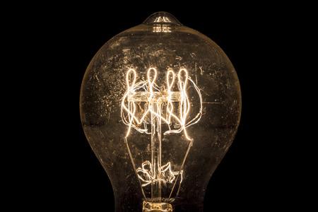 incandescent: Vintage incandescent light bulb filament on black.
