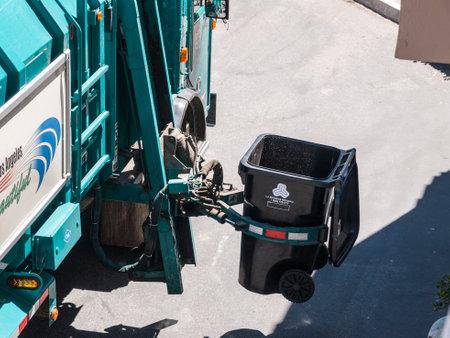 sanitation: Los Angeles, California, USA - July 13, 2010:  City of Los Angeles Department of Sanitation automated trash truck arm at work.
