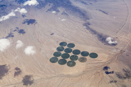 Aerial of green irrigated crop circles in a vast brown expanse of California's Mojave Desert.