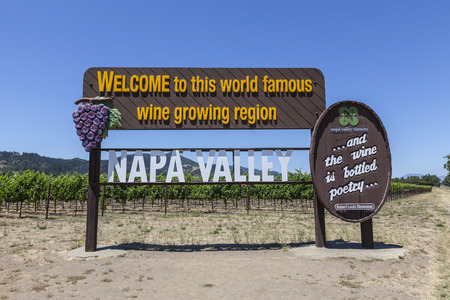 Napa Valley, California, USA - July 4, 2015:  Welcome to Napa Valley wine growing region sign and vineyards in central California. Publikacyjne