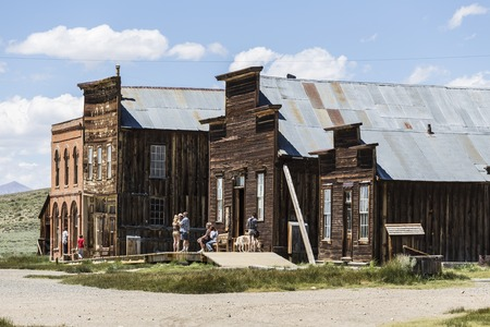 ghost town: Bodie, California, USA - July 6, 2015:  Summer tourists inspect historic structures at Californias Bodie State Historic Park.