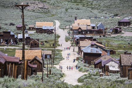western town: Bodie, California, USA - July 6, 2015:  Groups of summer tourists visiting Bodie ghost town in Californias Bodie State Historic Park.