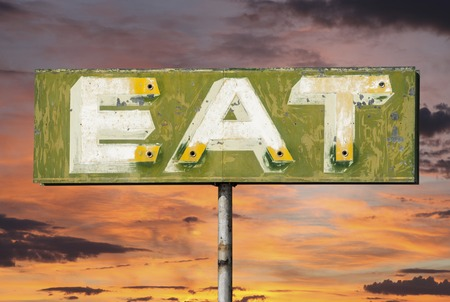 vintage sign: Faded vintage eat sign with sunset sky. Stock Photo