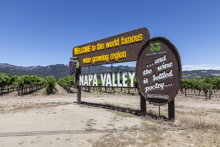 Napa Valley, California, USA - July 4, 2015:  Napa Valley wine growing region welcome sign and vineyards in central California. 報道画像