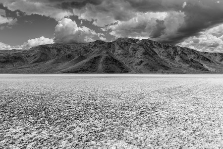 barstow: Mojave desert dry lake salt flat with dark storm clouds.