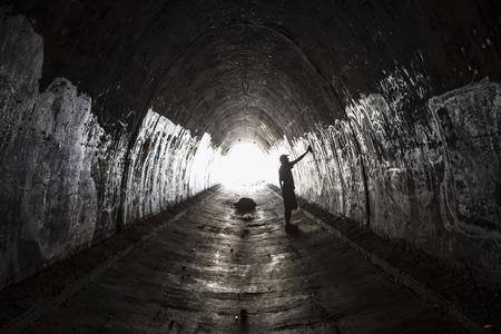 Graffiti artist at work in a grungy urban tunnel.