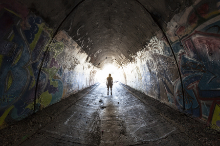 Dolina Simi w Kalifornii - 1 sierpnia 2015: Człowiek zwiedzający graffiti pokrył tunel pod autostradą 10 เลนową 118 w pobliżu Los Angeles. Publikacyjne