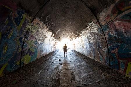Graffiti: Simi Valley California - August 1, 2015:  Man exploring graffiti covered tunnel under the 10 lane 118 freeway near Los Angeles.