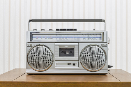 blaster: Vintage portable boom box style radio cassette player on old wood table.