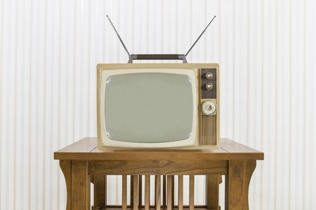 livingroom: Old television with antenna on wood table.