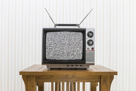Old portable television with antenna on wood table with static screen.
