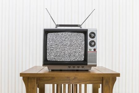 Oude draagbare televisie met antenne op houten tafel met statische scherm.