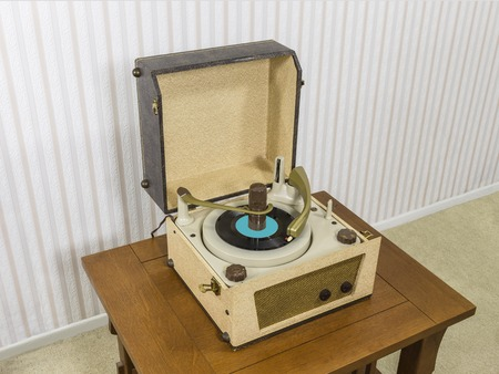 record player: Vintage 1960s record player on wood table.