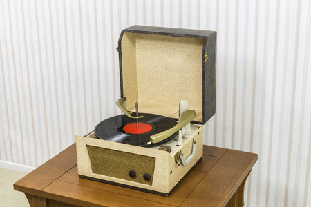 Vintage record player with vinyl album on wood table. Imagens