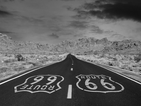 Route 66 black and white pavement sign with Mojave desert background.