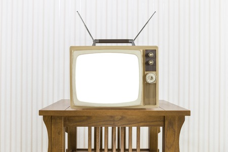 television: Old television with antenna on wood table with cut out screen.