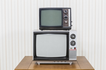 old fashioned tv: Vintage television stack on old wood table.