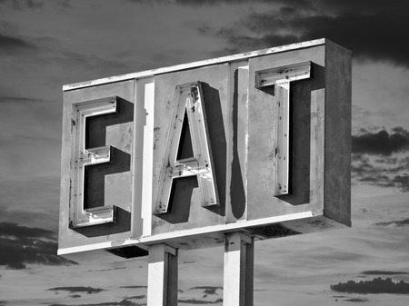 old sign: Vintage black and white eat sign with sunset sky. Stock Photo