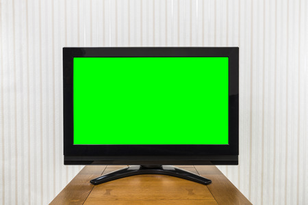 screen: Modern television on wood table with green chroma key screen. Stock Photo
