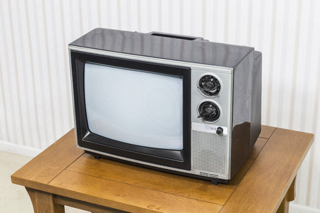 old fashioned: Vintage analogue television on old wood table.