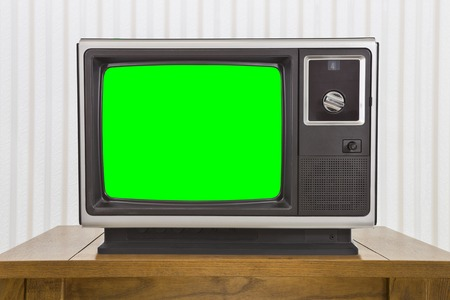 old fashioned tv: Old analogue portable television on table with green screen.