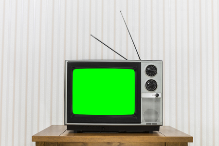 Old analogue television on wood table with chroma key green screen. Фото со стока