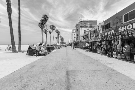 venice: Los Angeles, California, USA - June 20, 2014:  Editorial black and white photo of famously funky Venice Beach board walk in Los Angeles.