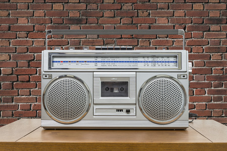 boombox: Vintage boombox on wood table with red brick wall.