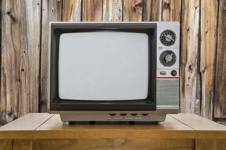 old fashioned tv: Vintage portable television and table with rustic cabin wall. Stock Photo